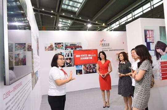 """担任志愿者的项目老师向参观者介绍""""美丽中国""""项目。"""