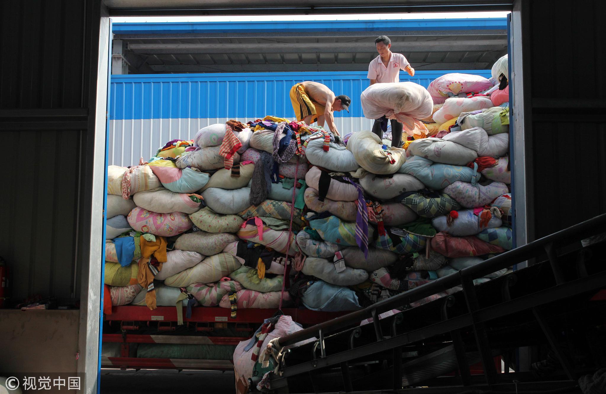 一辆装满一包包废旧纺织品的大卡车正在卸货。/视觉中国