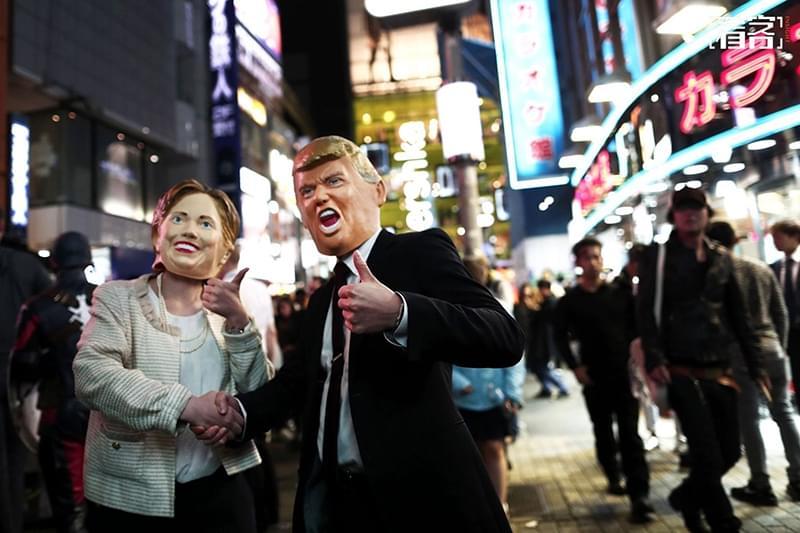 """图为当地时间2016年10月29日,日本东京,民众盛装参加万圣节游行,两名游行者头戴希拉里和特朗普的头套""""变装""""。(图:BEHROUZ MEHRI/视觉中国)"""