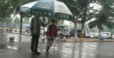 残疾老人遇降雨 邻居扛大伞为其遮雨