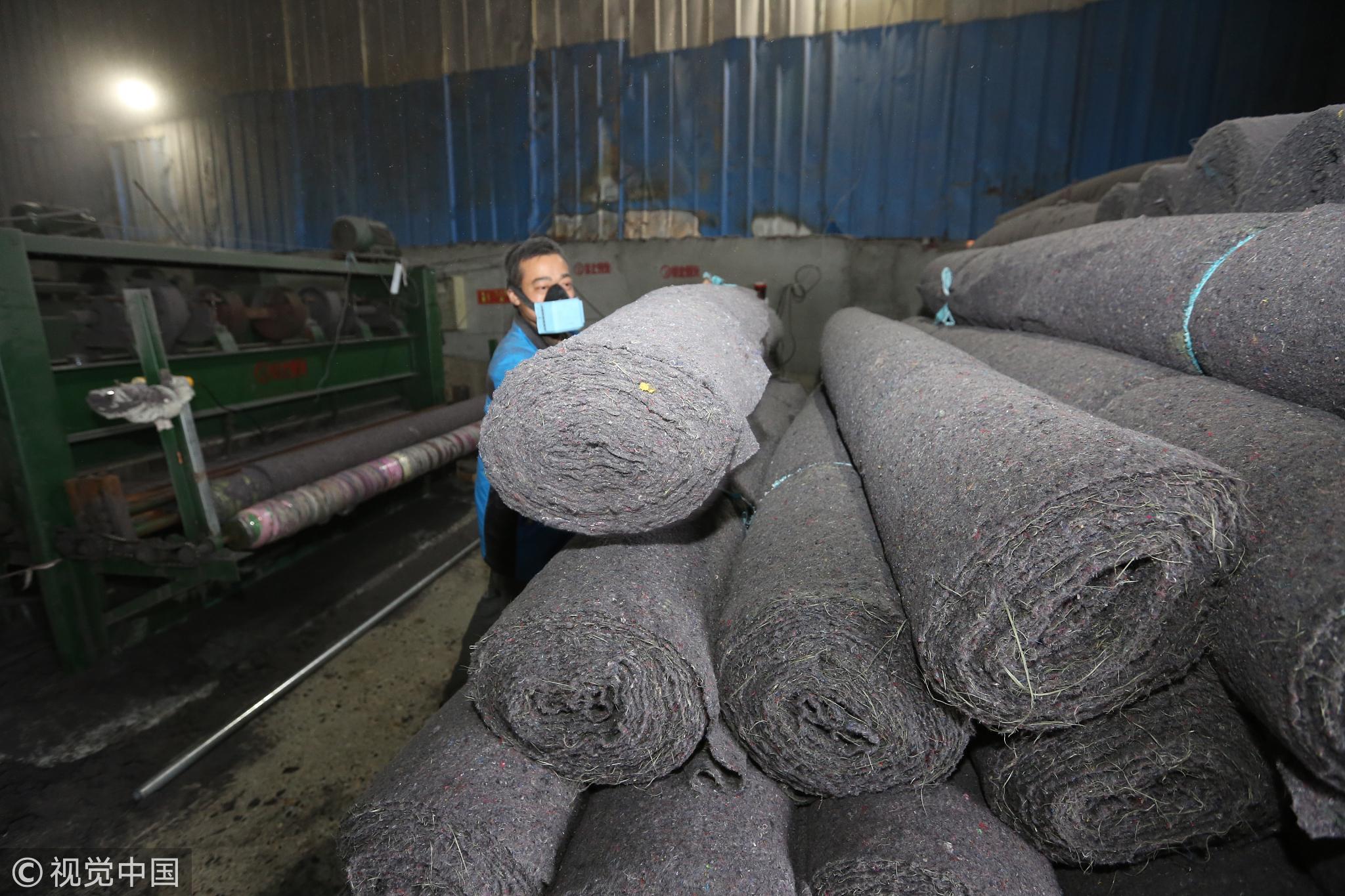 2016年10月13日,湖北省襄阳市,在分拣车间隔壁的生产车间,被淘汰的旧衣物经过粉碎、针刺等工序,变成一卷卷工业毛毡。/视觉中国