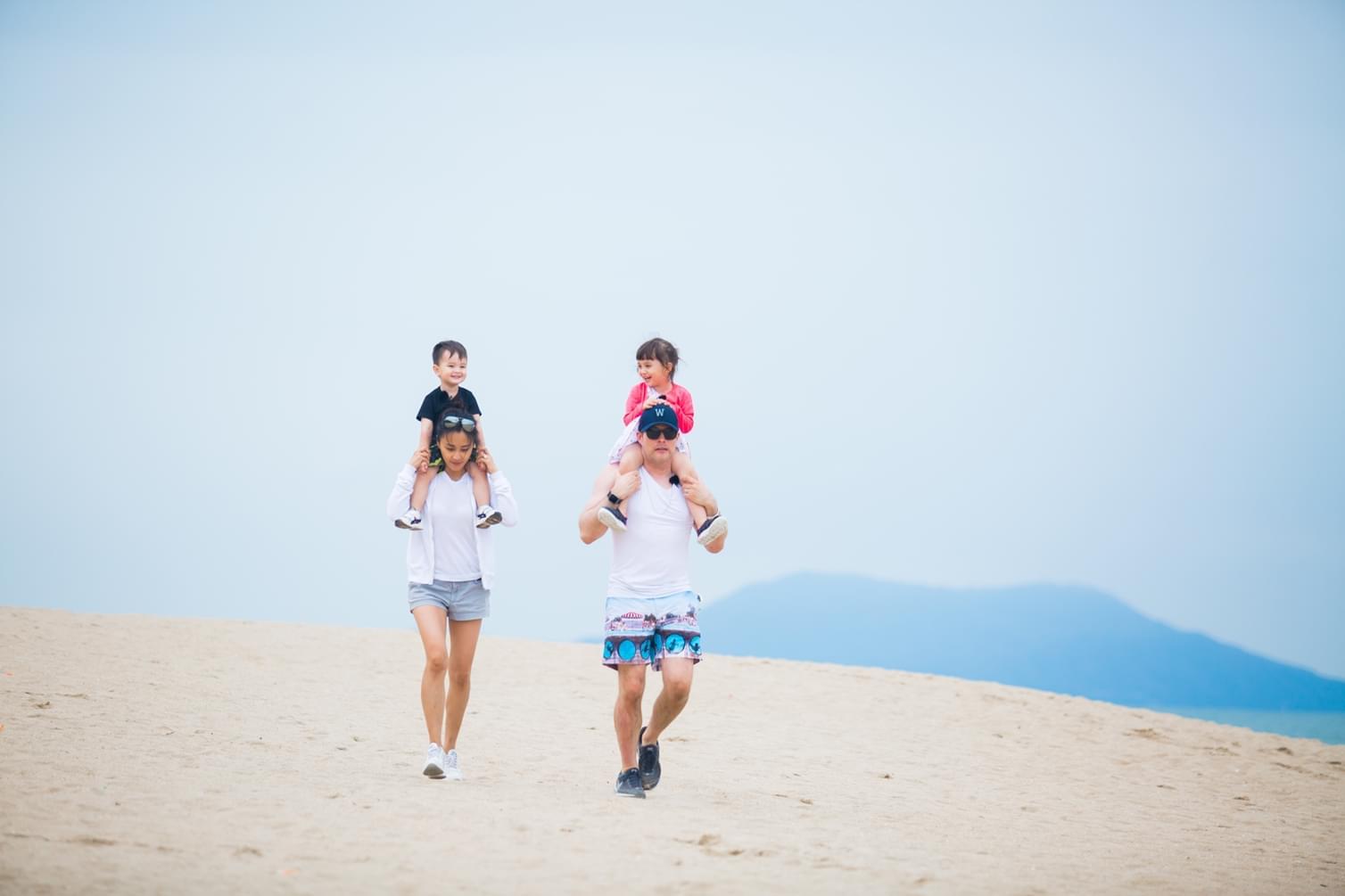 马雅舒一家四口在沙滩上漫步