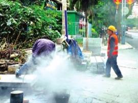 工人当街切割石块粉尘飘荡 加湿机却闲置一旁
