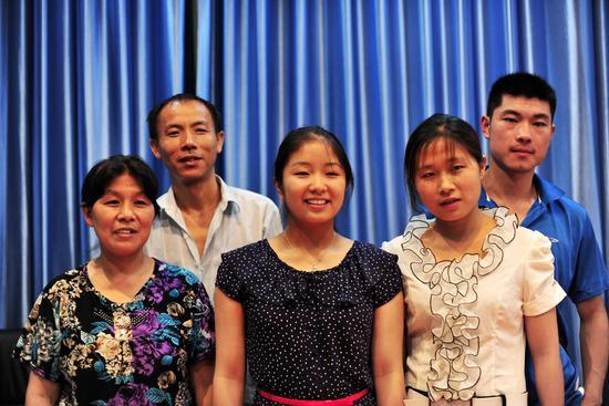 2012年6月6日,耶鲁高材生Jenna(中)和她的美国养母玛格丽特迎来第二批前来认亲的中国家庭,认亲结束后,Jenna希望和每一户家庭合影留念。/CFP