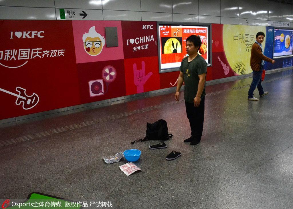 张尚武在地铁通道内卖艺乞讨
