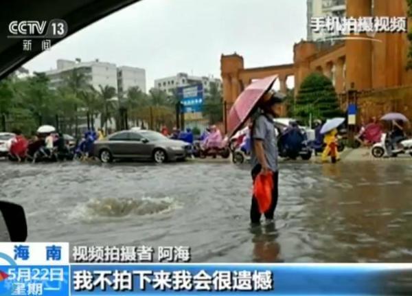 一位老人冒雨守在旁边引导过往行人车辆避开危险