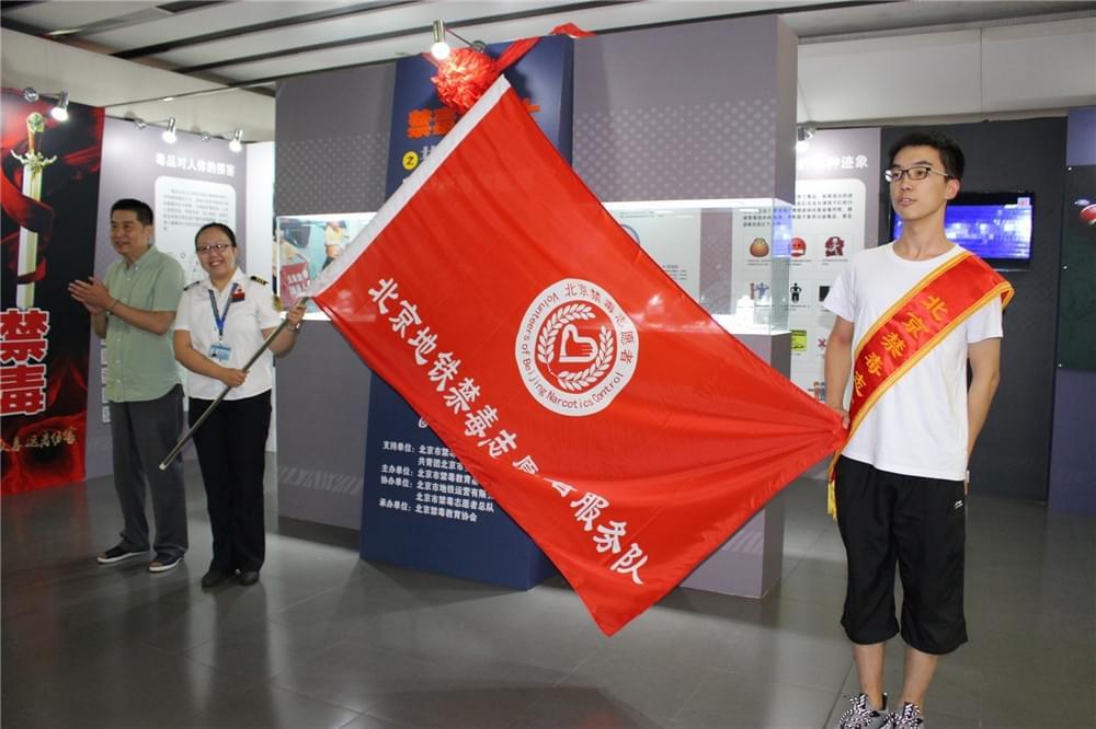 北京市禁毒教育基地管理中心副主任、北京禁毒志愿者总队常务副总队长石建春(左一)为北京地铁禁毒志愿服务队授旗