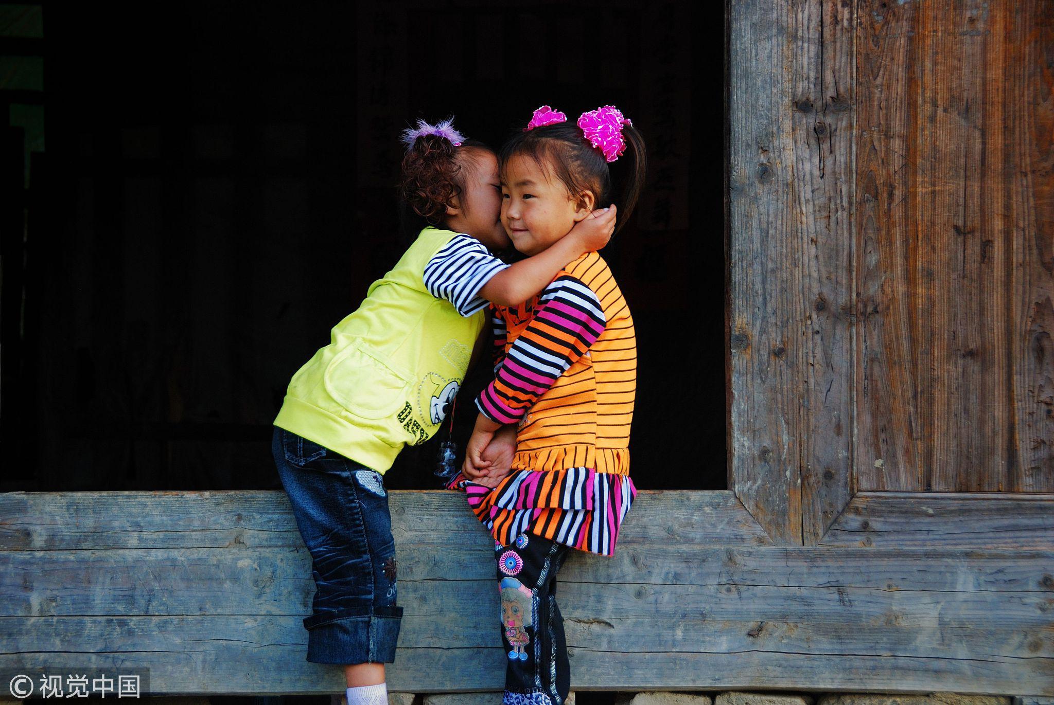 湖南邵阳,两个小女孩坐在门槛上讲悄悄话 / 视觉中国