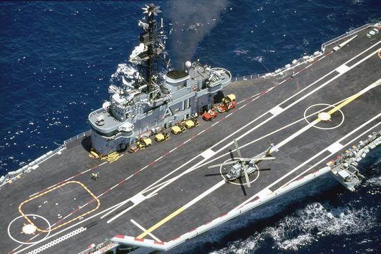 """""""米纳斯吉拉斯""""号中部近景,可见左舷加装的8.5度斜角甲板和右侧不规则的外飘结构。一架""""美洲狮""""直升机正在做起飞准备"""