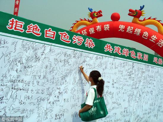 """2008年6月3日,湖北宜昌举行""""拒绝白色污染,使用环保布袋""""的万人签名活动/视觉中国"""