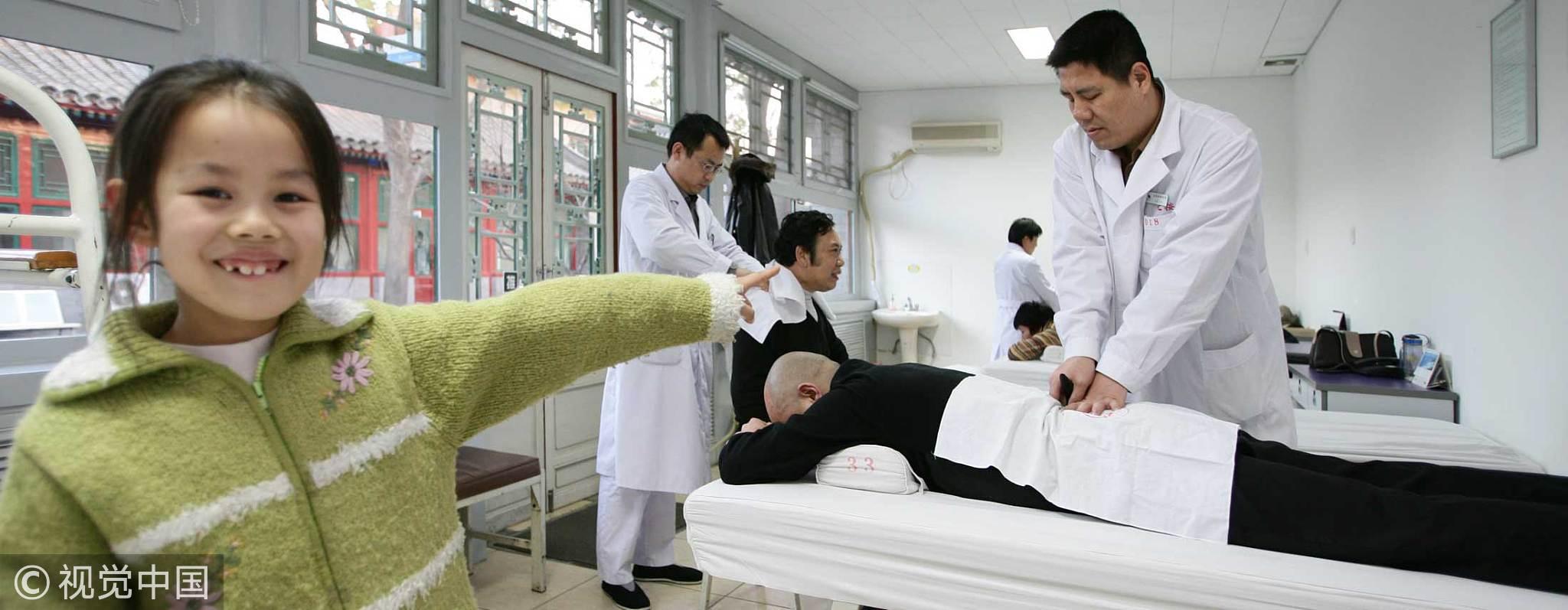 2005年12月1日,北京按摩医院,小姑娘的盲人爸爸正在为人按摩。/视觉中国