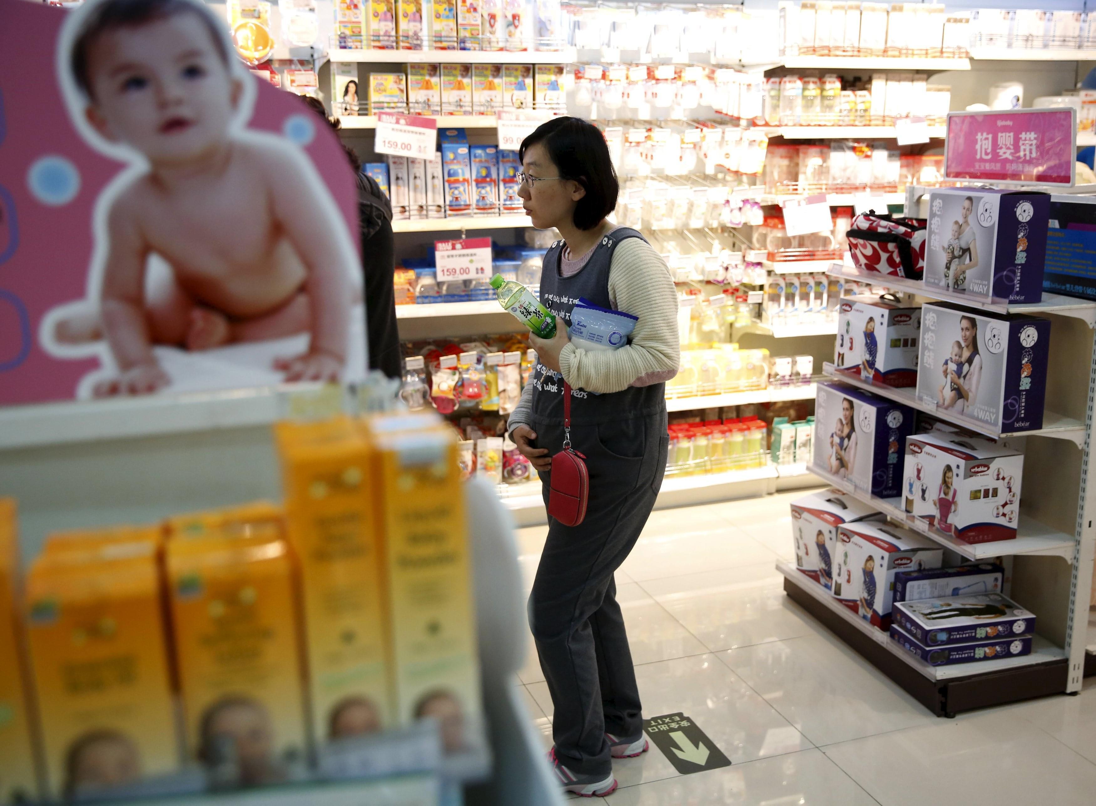 2015年10月30日,北京,一位准妈妈在商店内挑选育婴用品。/视觉中国