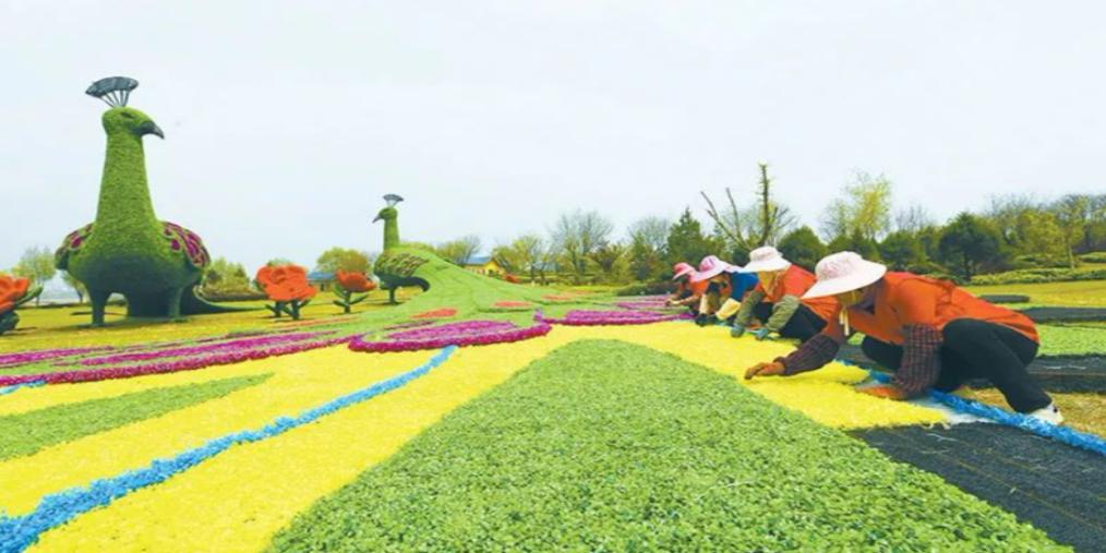 襄垣县:工人们正在铺设仿真植物雕塑