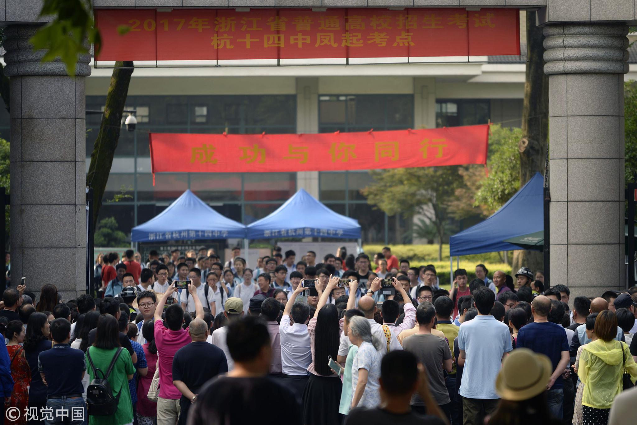 2017年6月7日,高考首日考试结束,杭州第十四中学考点外,等候在考场外的家长用手机记录考生走出考场的一刻 / 视觉中国