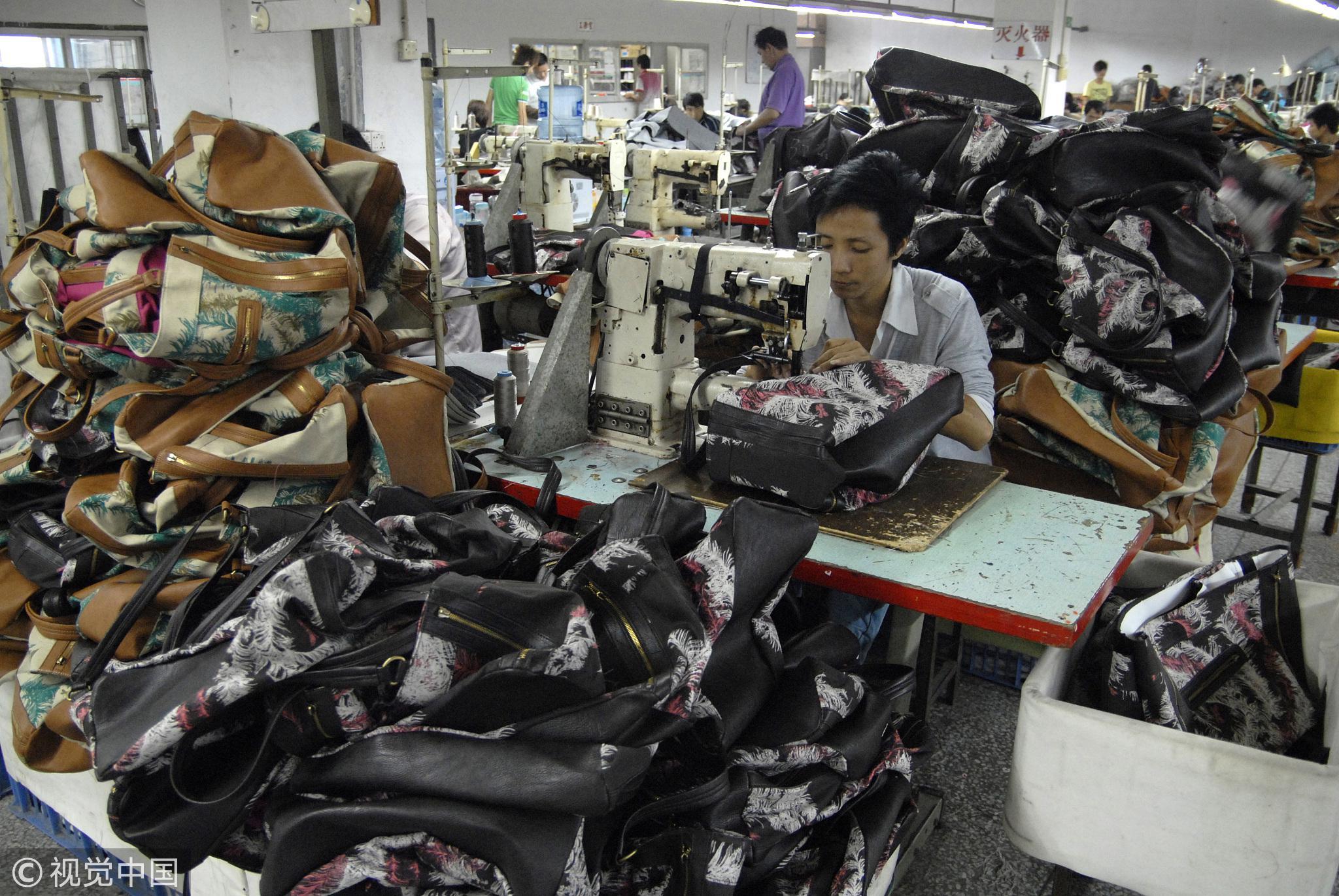 2011年,广东省东莞市长安镇,三来一补企业的工人正在岗位上缝制手袋/视觉中国