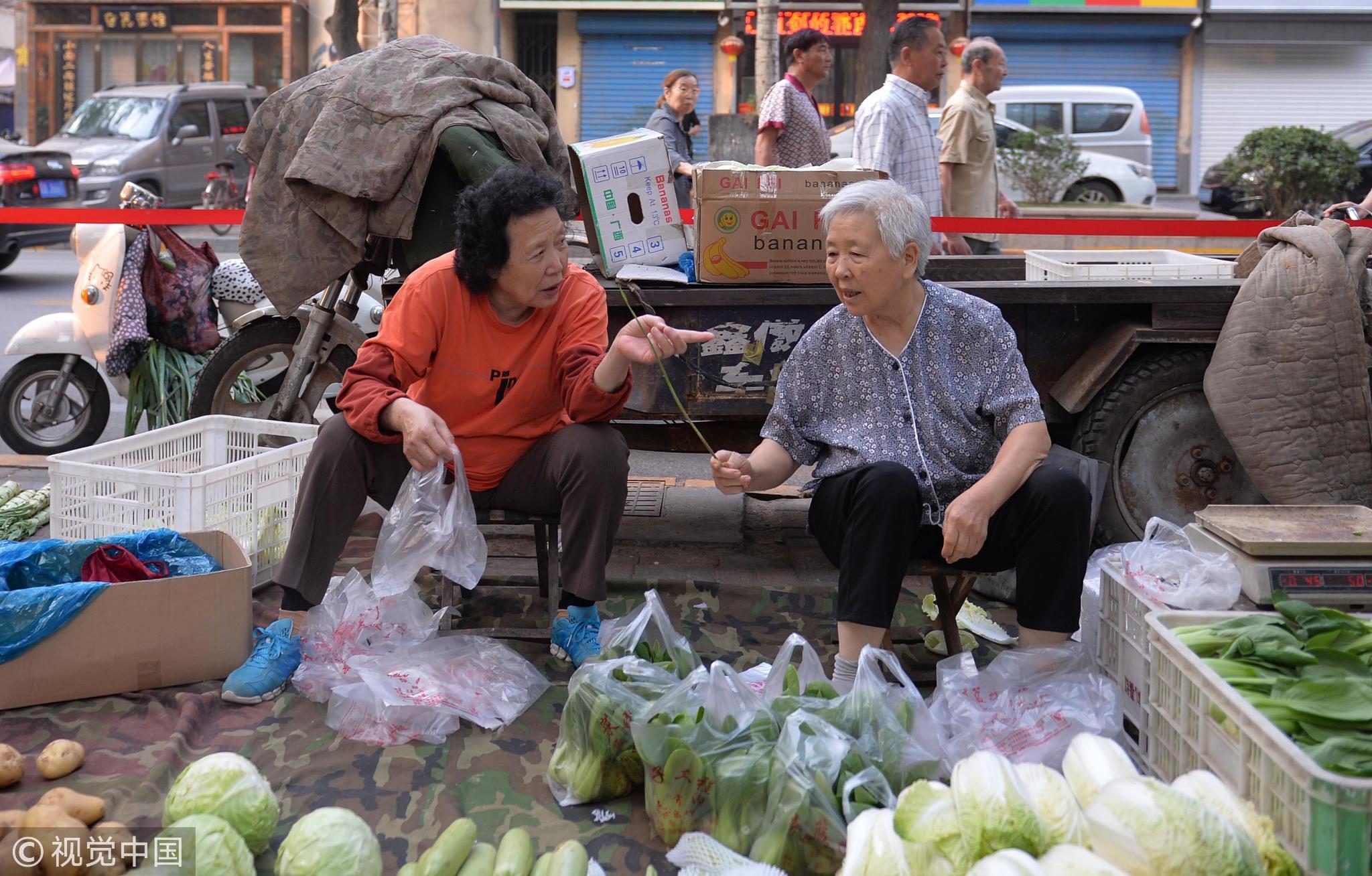 石家庄,两位奶奶在菜市上聊天。她们过去是邻居,如今好不容易见一面,两人在聊过去的熟人 / 视觉中国