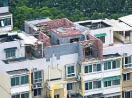 60多户业主楼顶加盖房屋还未拆 天井里又装电梯