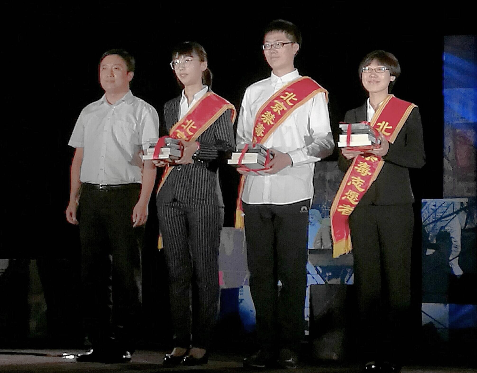 2、北京团市委副书记王洪涛代表团市委向禁毒志愿者赠送禁毒光盘、图书