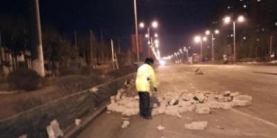 货车散落石块埋隐患 交警借铲车清理路面