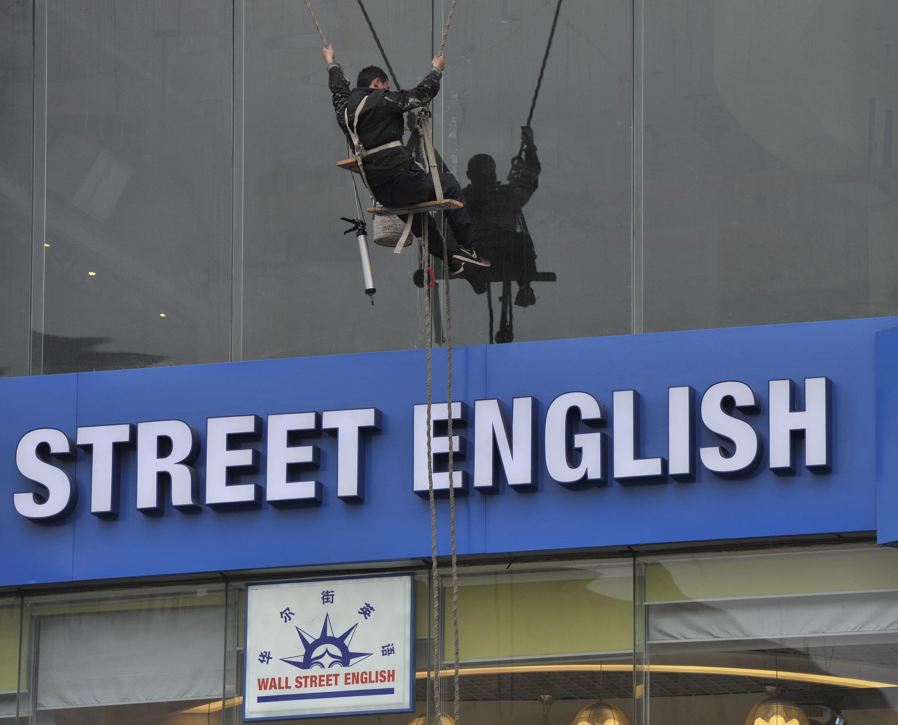 2012年02月29日,江苏省南京市,工人在清洗一家英语培训机构的外墙。 /CFP