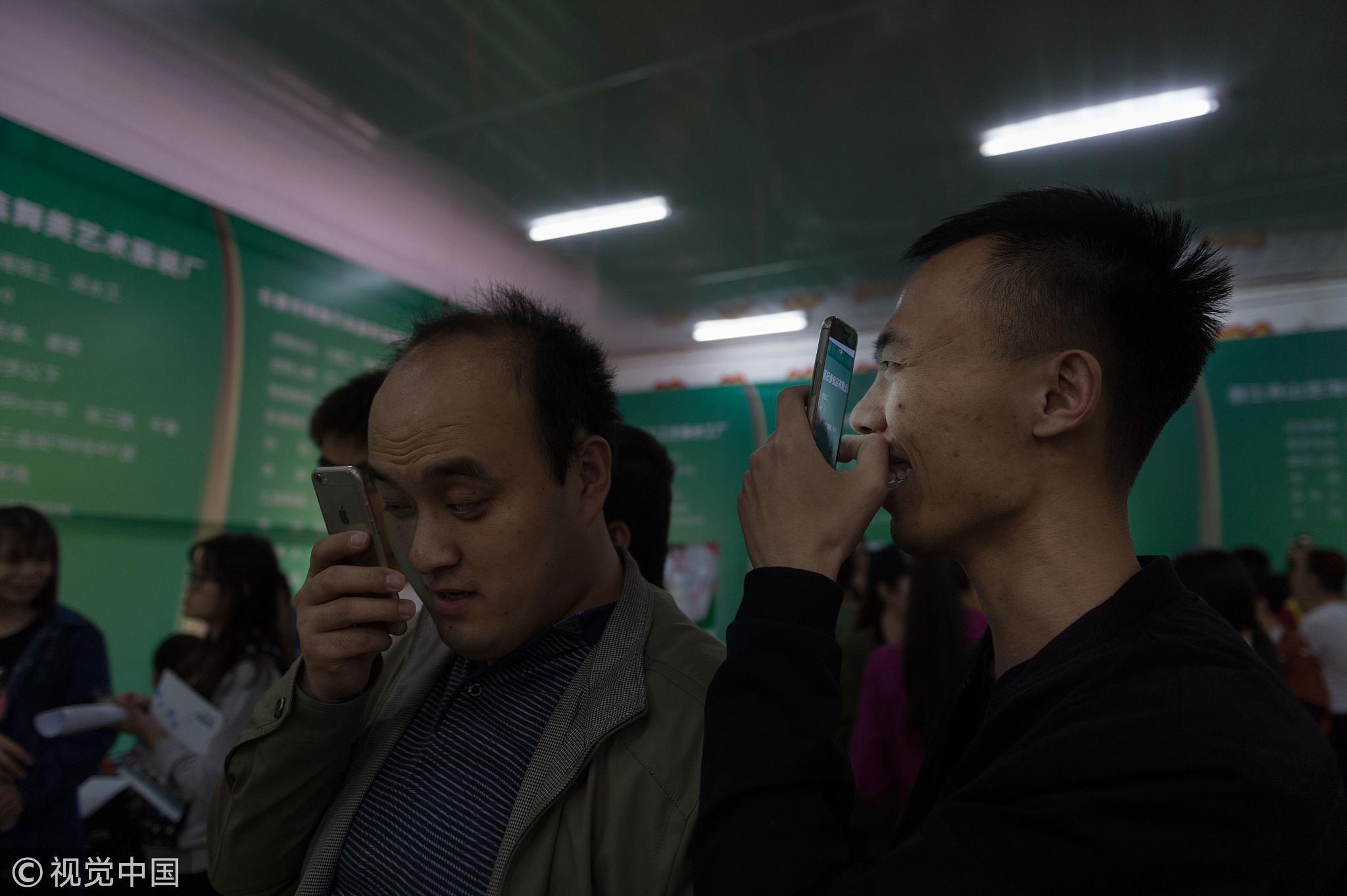 2016年5月26日,长春,专场招聘会上,盲生正在借助手机寻觅合适的工作。/视觉中国