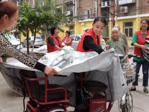 邯郸一社区给有三轮车的老人发放车衣