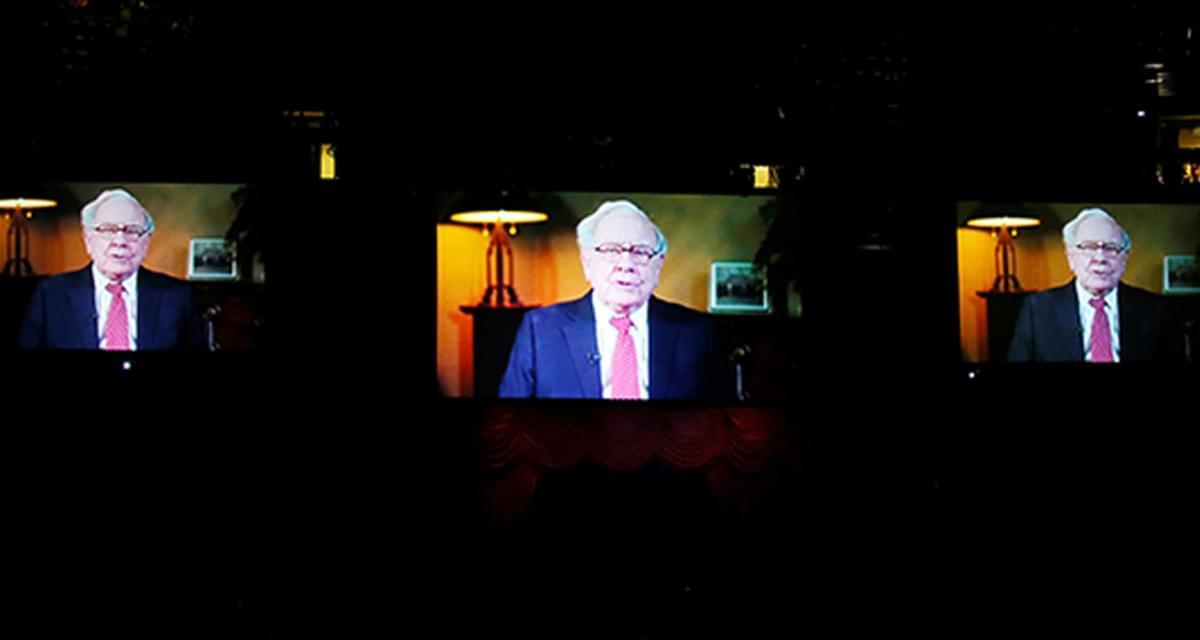 会场大屏幕上显示巴菲特回答提问的画面