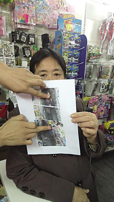 店主官先生的母亲在展示监控拍下偷拿东西的小朋友