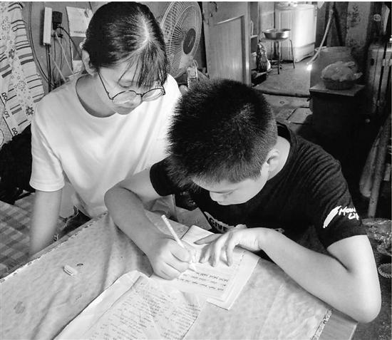张丽莹辅导弟弟做作业。
