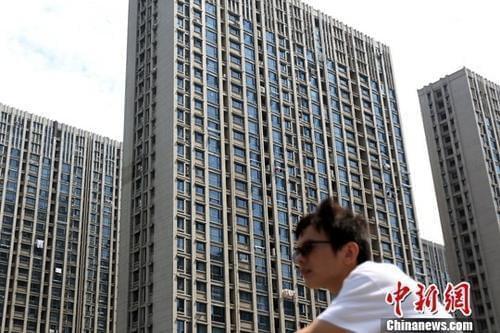资料图:市民从南京一处楼盘前经过。<a target=