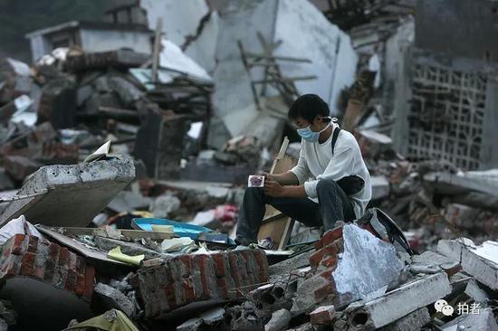 2008年6月23日,北川县城,一名抗震救灾的志愿者在废墟上寻找灾民留下的照片作为纪念。摄影/薛珺