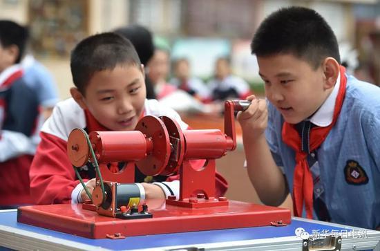 """2018年9月18日,石家庄市草场街小学的同学们在体验""""磁力发电""""小实验,探索科学的奥秘。新华社发(章朔 摄)"""