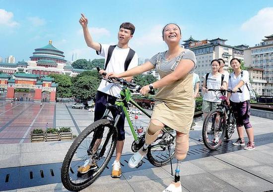 """昨日,大学生志愿者带""""微笑女孩""""高莹看人民广场和三峡博物馆。记者"""