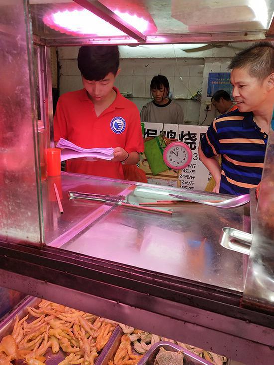 队员程浩请教一位开店二十余年的老板,讨论盐焗鸡美食文化的传承