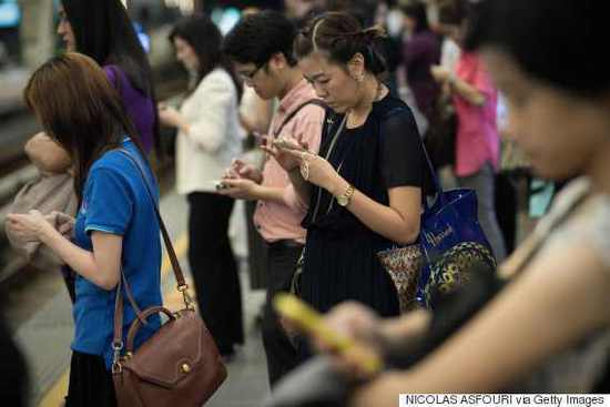 This picture taken on March 19, 2013 shows people using their smartphones on the platform of a BTS train station in Bangkok. A recent Facebook-sponsored study showed smartphone owners are often connected all day. People can be found glued to their smartphones at airports, on trains, in restaurants and even while walking on the street, creating a disconnection from their immediate surroundings. Smartphone sales are expected to continue to surge in 2013 with some 918 million units to be bought worldwide. AFP PHOTO/ Nicolas ASFOURI (Photo credit should read NICOLAS ASFOURI/AFP/Getty Images)