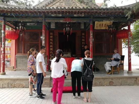 桃花山的寺庙里,考生家长陪孩子前来求保带。王双兴 摄