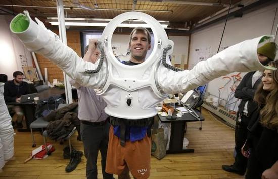 Andrzej Stewart, the chief engineering officer on a year-long Mars simulation mission that ended in August, puts on a new space suit at the Rhode Island School of Design (RISD) in Providence, R.I. RISD created the new space suit for scientists to wear on the next Mars simulation mission in 2017 in Hawaii.