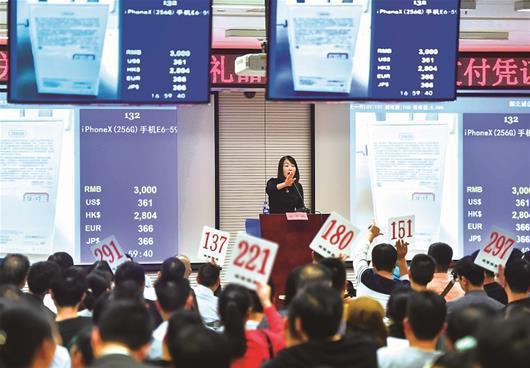 图为:昨日,武汉市公务人员上缴礼品第四次专场拍卖会在武汉市民之家举行,引来众多市民竞拍,图为拍卖现场。 楚天都市报记者萧颢摄   图为:竞拍者争相举牌