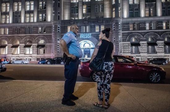 """""""警察联络员""""曼莎・米勒(Samantha Miller)与特区警察在酒店对面交谈。(图源:华盛顿邮报)"""