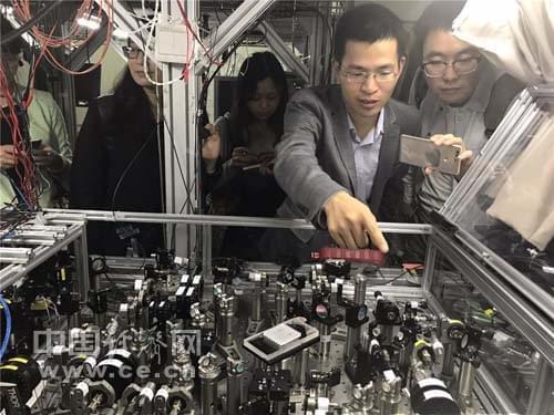 朝阳教授(右二)在实验室向记者们介绍世界首台超越早期经典计算机的光