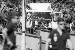 7月15日,在法国尼斯,警察从袭击事件现场的卡车前走过。据法国媒体15日报道,法国警方已通过指纹分析正式确认14日晚在尼斯驾驶卡车冲撞人群的疑犯身份,与此前在卡车内发现的身份证件相符。