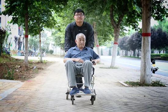 带瘫痪父亲上大学的男孩毕业了 父子俩一齐领证