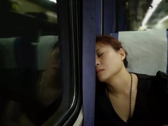 关桂侠在承德前往石家庄的火车上睡着了。刑满释放后,她每个月都要来石家庄几趟,来给还在服刑的妈妈和姐姐送东西。新京报记者段睿超 摄