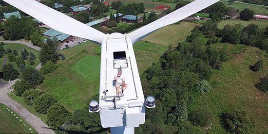 无人机拍下惊悚瞬间男子爬风车上晒太阳