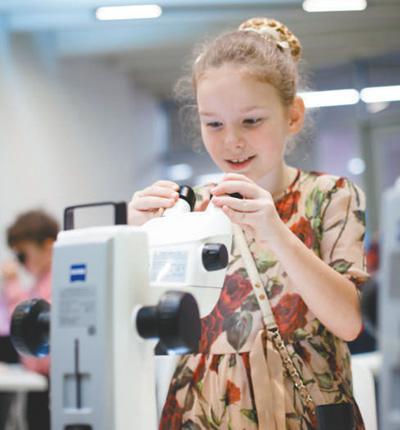 俄罗斯小学生索菲娅在莫斯科的一家科技馆里学习使用显微镜。资料图片