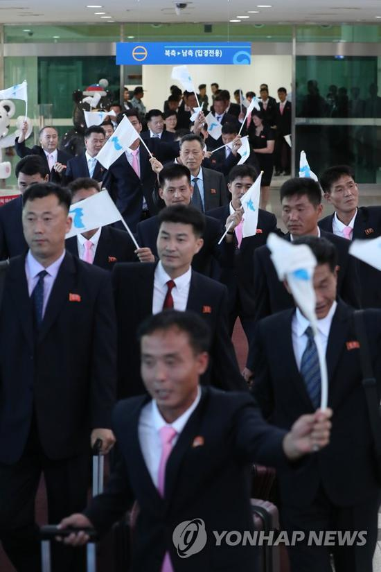 8月10日,朝鲜代表团抵达韩国,挥舞统一旗。(韩联社)