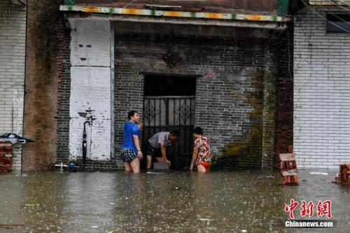 9月17日,广东江门台山大江镇侨园新村,民众使用铁板抵挡家门口的积水。中新社记者陈骥?F摄