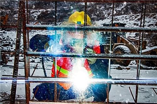 冒雪对隧道支护所需的钢结构护架进行焊接