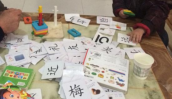 一个幼儿在一堆卡片中找出家长所说的汉字。视觉中国 资料
