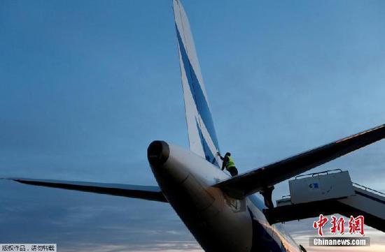 一名工作人员正在检查这架被损坏的飞机.jpg